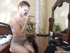 Обнаженная русская девушка перед зеркалом наделает капроновые колготки