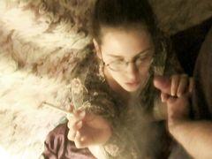 Интересная девушка в очках курит и сосет член своего возлюбленного