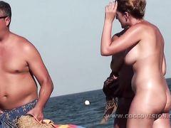 Голые девушки на пляже не замечают камеры в руках вуайериста