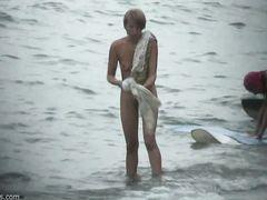 Вуайерист подсматривает на пляже за голой красивой блондинкой